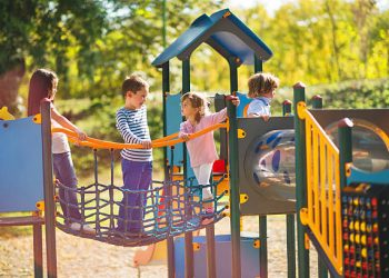 Small group of children having good time at jungle gym and talking.